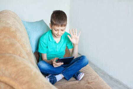 Child boy using digital tablet and makes video call on sofa in living room.