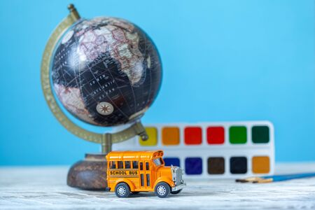 Back to school concept. Yellow school bus toy model and empty blank with globe and school supplies