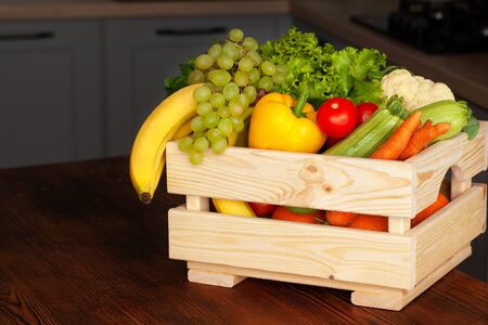 Full box with fruits and vegetables on the kitchen table. The concept of healthy and wholesome, organic food.