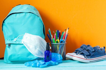 Blue School backpack with mask, hand sanitizer, gloves and stationery on table on orange background. New life after Pandemic COVID-19 concept. Zdjęcie Seryjne