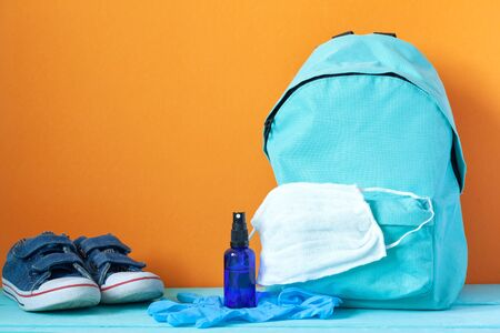 Blue School backpack with mask, hand sanitizer, gloves and stationery on table on orange background. New normal life concept. Zdjęcie Seryjne