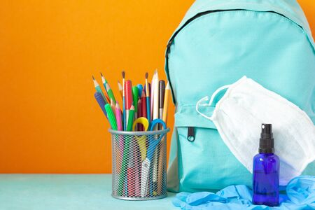 Blue School backpack with mask, hand sanitizer, gloves and stationery on table on orange background. New normal life