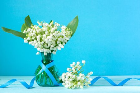 Bouquet of white lilies of the valley in glass vase on turquoise background. Template of greeting postcard.