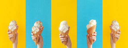 Child holding a vanilla ice cream cone on a bright yellow and blue background. Sweet dessert decorated with colorful sprinkles, closeup. Banner