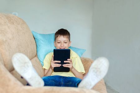 Child boy using digital tablet on sofa in living room. Kid studying from home and playing with gadget