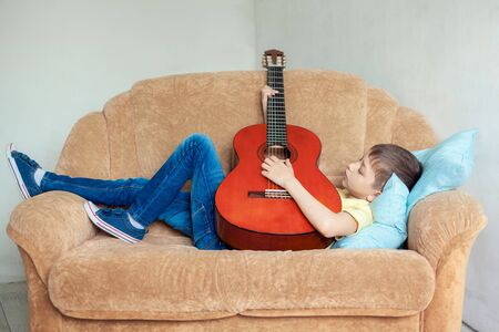 Boy playing guitar in his room lying on sofa. Relax and rest concept.