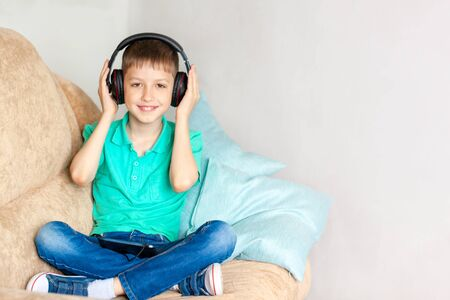 Happy smiling kid boy in headphones listen to music or audiobook in living room. Boy studying homework during his online lesson at home, social distance during quarantine.