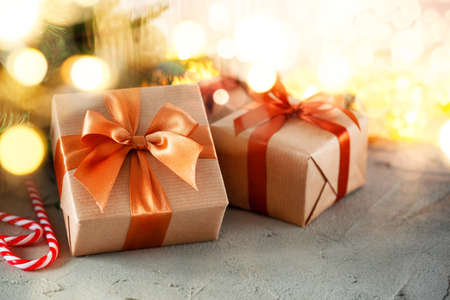 Rustic retro gifts, present boxes on bokeh background. Christmas time. Handmade paper wrap.