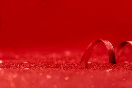Minimalistic red ribbon decor on red shiny glitter holiday beautiful background. Selective focus. Festive concept. Standard-Bild