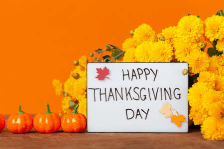 Thanksgiving autumn composition with yellow flower and pumpkins on orange background. Lightbox with the phrase Happy thanksgiving day. Autumn holidays, fall concept. Standard-Bild
