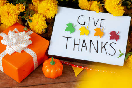 Creative orange box. Thanksgiving autumn composition with yellow flower and pumpkins. Lightbox with the phrase Give thanks. Autumn holidays, fall concept. Standard-Bild