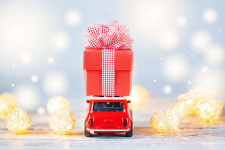 Red toy car carrying on roof ared gift box on winter background. Christmas and new year concept. Back view. Standard-Bild
