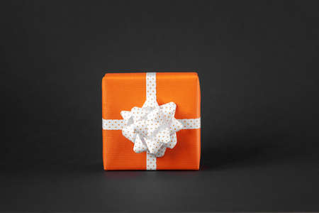 Wrapped handmade present in orange paper with bow on black background. Present box with copy space. Standard-Bild
