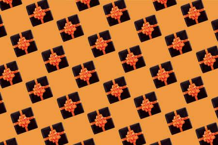 Black gift box on orange background. Halloween concept, Creative design. Pattern. Standard-Bild
