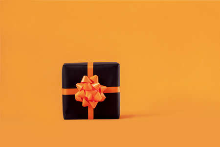 Wrapped handmade present box in black paper with bow on orange background. Halloween and Birthday concept.