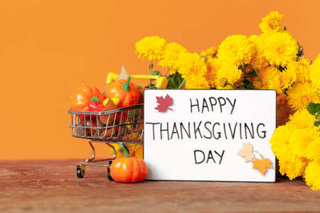 Thanksgiving autumn composition with yellow flower and shopping cart with pumpkins and acorns on orange background. Lightbox with the phrase Happy thanksgiving day. Autumn holidays, fall concept.