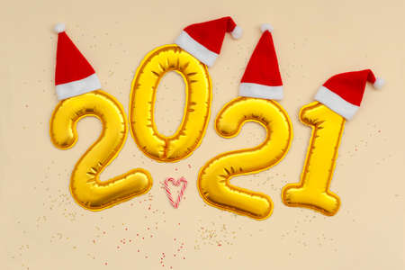 Happy New Year Golden digits 2021 numbers with christmas hat on beige background with confetti. New Year or Merry Christmas concept. Standard-Bild