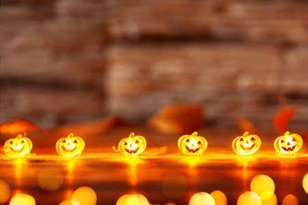 Garland of glowing halloween pumpkins on dark wooden background with copy space. Halloween background.