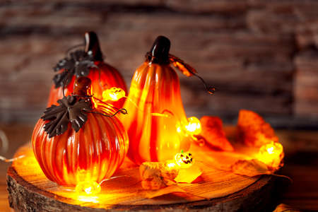Holiday decoration with decorative ceramic pumpkins with decoration light Garland of glowing on wooden table. Halloween background.