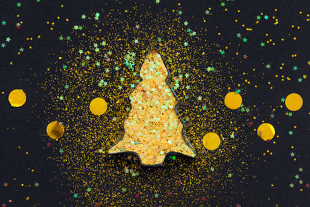 Christmas tree shaped cookie cutter with golden sparkles star confetti on black background. Flat lay style. Standard-Bild