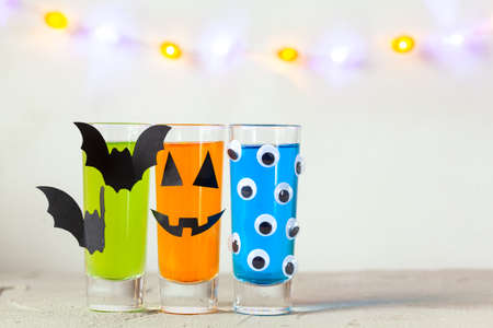 Cute Halloween drinks for a kids party. Three colorful juice in glass deacoration paper bat and eyes on light background copy space