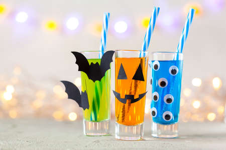 Cute Halloween drinks for a kids party. Three colorful juice in glass deacoration paper bat and eyes on light background with copy space