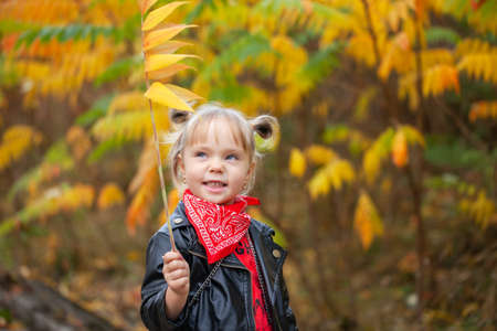 Happy smiling blonde girl holding yellow red leaves in sunny autumn park. Child playing in park at autumn. Kid gathering yellow fall foliage.