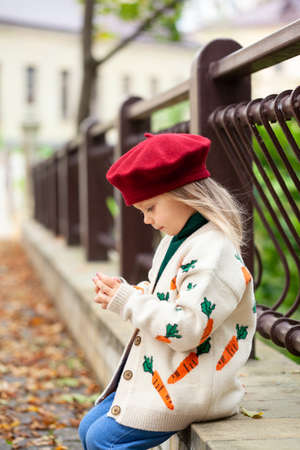 Beautiful blonde girl in sunny autumn park. Child playing in park at autumn. Autumn mood.