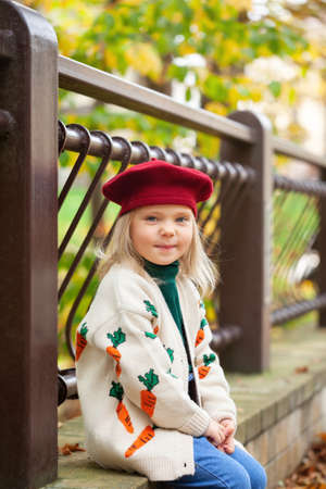 Beautiful smiling blonde girl in sunny autumn day. Child playing in park at autumn.