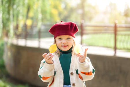 Portrait little smiling girl holding yellow leaves in sunny autumn day. Child in red beret and warm sweater in autumn park.