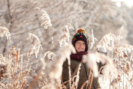 Wintertime. Cute boy having fun playing with fresh snow in winter forest. Active leisure outdoors for kid in snowy winter day