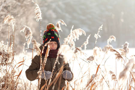 Wintertime. Cute boy walking in winter forest. Active leisure outdoors for kid in snowy winter day