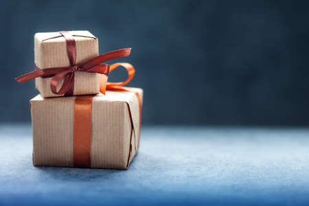 Holidays present or gift boxes with brown ribbon on dark background with copy space.