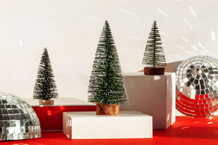 Trendy composition Christmas trees and Santa Hat on podium on neutral background. New Year concept.