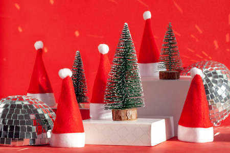 Trendy composition Christmas trees and Santa Hat on podium on red background. New Year concept.