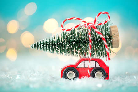 Toy red car with a Christmas tree on the roof on a bokeh festive blue background. Christmas and New Year concept Standard-Bild