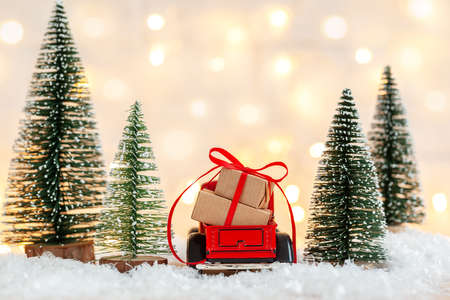 Red toy car truck with Stack of Christmas gift boxes aginst netural background with christmas trees. Holiday greeting card. Back view. Stock Photo