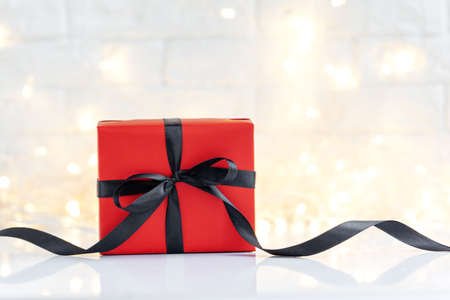 Red gift box with black ribbon on white light background with copy space for text. Black Friday concept. Stockfoto