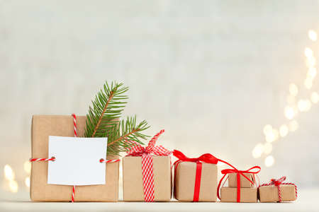 Christmas handmade gift box decorated with evergreen branch and empty blank gift card and different Christmas gift boxes with red ribbon.
