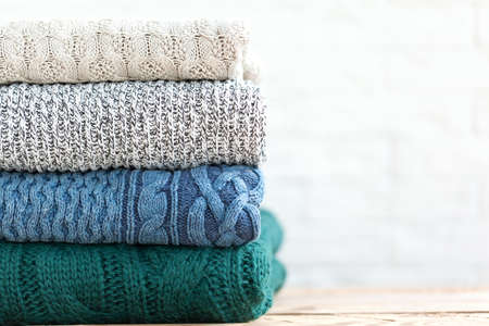 Stack folded of cozy knitted sweaters on white and wooden background Stock Photo