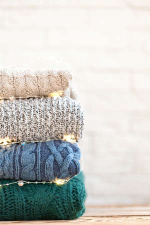 Stack of wool knitted clothes on wooden table on wite background with festive bokeh.