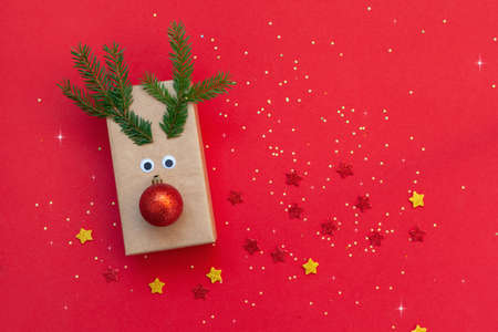 Creative Christmas gift box in the form of a deer against a red background. Holiday greeting card
