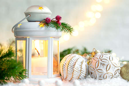 Christmas decoration lantern with burning candle and cristmas balls on light festive background.