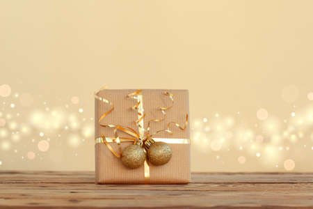 Christmas gift box or present decorated golden ribbon and two balls on neutral background with boke