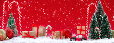 Festive composition Christmas red car with a gift box in a pine forest where many different presents on red background. Happy New Year card concept. Banner.