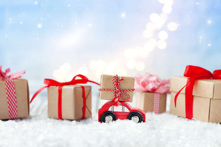 Red toy car with a gift on the roof among the Christmas gift boxes on blue backgroun with boke. Festive greeting card.