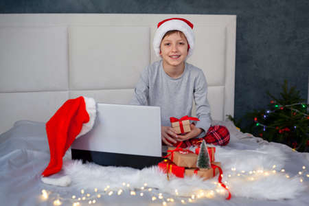 Happy little boy child in red santa hat at home in bed with laptop and christmas gift boxes.Christmas online greetings.