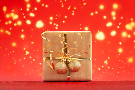 Christmas gift box or present decorated golden ribbon and two balls on red background. Holiday concept. Stock Photo