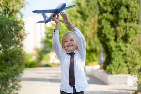 Handsome child boy with toothless smile in white shirt plays with toy airplane on outdoors. Dreams on new Travel and adventure. Stock Photo