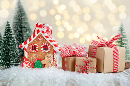 Gingerbread house with many gift boxes on wooden background. Symbol of Christmas and winter holidays.